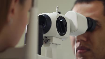 wzrok : close up shot of the mans face, the person is working as an ophthalmologist in a private clinic and checks the eyesight for the patients, the doctor conducts biomicroscopy of the eyes