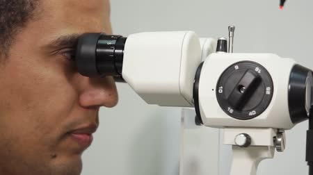 optyk : Close up shot of male oculist examining eyes using slit lamp biomicroscopy. Problems with eyes.