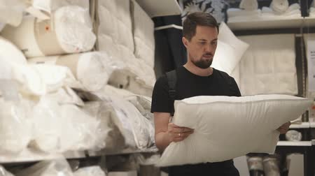 mikrohullámú : a young man who is in the mall examining different pillows, it is important for him to choose softness and determine the composition, the gentleman prefers the natural filling Stock mozgókép