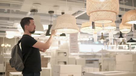 mikrohullámú : an adult male examines floor lamps for lamps, a gentleman who is in the mall looks at the lamp in order to determine the level of light in his apartment