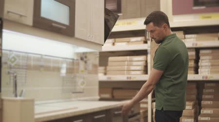 mikrohullámú : a young man looks at the wooden door from the kitchen shelf, he looks at the quality of the commercial furniture, the gentleman chooses the shelving for the house