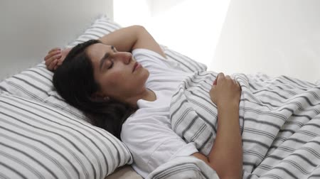 flat head : a young and pretty woman lies in a bed with her eyes closed, her head is on the pillow, and the body is covered with a blanket, the woman is sleeping Stock Footage