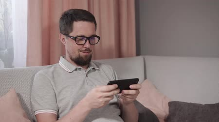 幼稚な : Childish bearded man in glasses playing games on smartphone sitting on couch. Man is happy playing online games. 動画素材