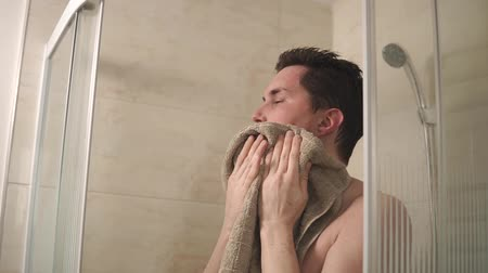 erkek güzellik : portrait of a young and handsome man who wipes his wet hair and face with a terry towel, the gentleman is clean and is going to go on business Stok Video