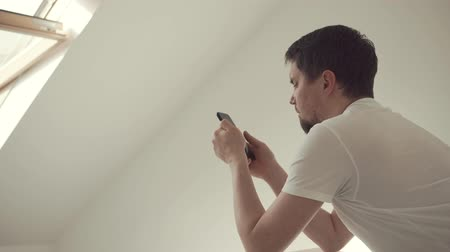 kettyenés : a modern guy is online learning through a smartphone in his apartment, a stylish man is holding a fashionable gadget in his hands in his minimalistic apartment