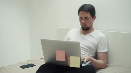ileri : a young man sits on the sofa in his apartment and prints the text on the laptop, next to him is the phone to answer the calls, the gentleman works as a freelancer Stok Video