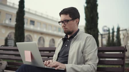 o : an adult graduate student writes a thesis for university studies on a laptop, a man concentrates on his online training, he sits on a park bench Stok Video