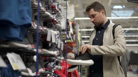 потреблять : Casual guy looking for new sneakers in a store. Man searching for comfort sneakers for daily usage. Black sports shoes.