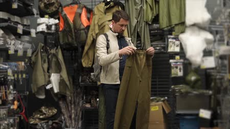 посетитель : Male shopper is applying to himself pants in a clothing store. He is taking it in hands, rotating and examining, choosing size