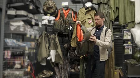покупатель : Grown man looking for new lifejacket in sports shop. Male fisher buys new camouflage jacket for fishing. High-quality equipment.