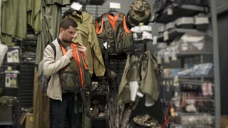 roupas : Adult man is rotating a life jacket in a trading hall of a sport store. He is choosing protective and supportive accessories for traveling and activities