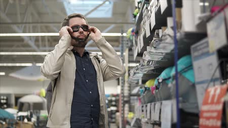 levou : Bearded man is taking swimming goggles from rack in a shop and applying it on his face. He is looking from glass, then taking other and comparing them both