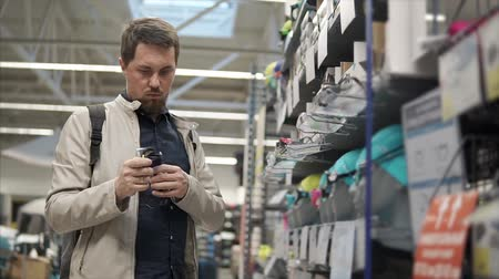 comparar : Adult man choosing new swimming goggles in a sport shop. Bearded man holding and checking for quality goggles. Swimming equipment. Stock Footage