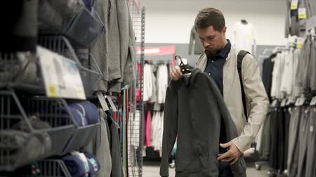 roupas : Male shopper is holding hanger with sporty sweatshirt in a store. He is examining quality and style, standing in a trading hall in big mall Stock Footage