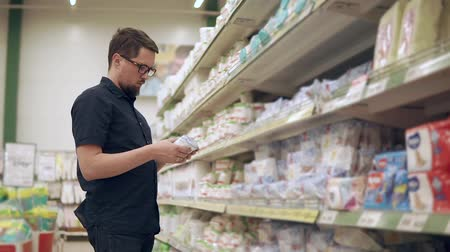 покупатель : Bearded dark-haired man is choosing wipes in a hypermarket hall. He is reading prices and inscriptions on a packs, thinking and deciding