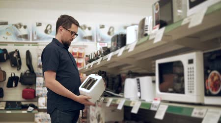 meio : Man is watching on a rack with electric toaster and taking one of them in hands. He is reading labels and looking on a costs in a sales area Stock Footage