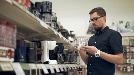 coffee maker : Adult man is rotating a detail of electrical coffee-machine in a trading floor of a shop. He is putting it on a shelf and getting coffee-maker