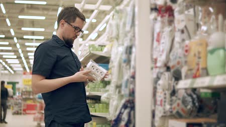 adaptador : Male customer is learning pack with electric socket in a trading floor of big shop. He is regarding it and looking on a rack with different kinds Stock Footage