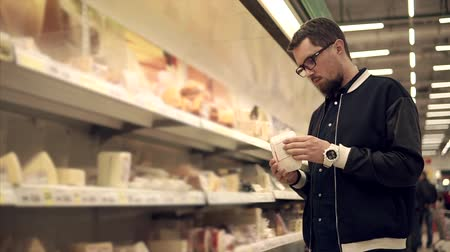 посетитель : Male customer is a watching on a shelf with foodstuff in a store. He is taking cheese, looking on it and putting it back, then choosing a piece of meat