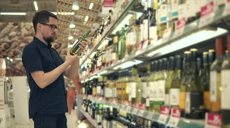 вред : Adult man in glasses trying to choose right bottle of wine for the night. Choosing between bottles of white wine. Shopping in supermarket.