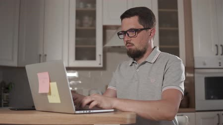 cansado : Man with glasses is working with notebook in kitchen. He is using keyboard and looking on a display, taking off spectacles and resting