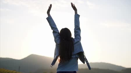 head over : Young woman is rejoicing a sunrise over mountains. She is rising hands up and looking on a picturesque tea plantation, back view Stock Footage
