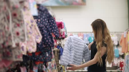 buyer : Cheerful woman is walking near hangers with jackets for kids in a clothing store. She is taking one and examining it, then moving further