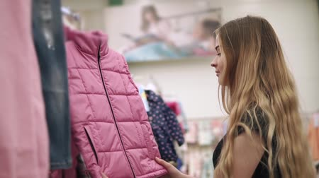 abiti appesi : Beautiful blonde woman looking for new clothes in a shopping mall. Woman walking in aisle with warm clothes. Stylish pink vest.