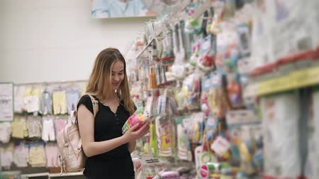 супермаркет : Young woman is choosing a toy for her child in big store in a mall. She is rotating in hands package with play sand kit Стоковые видеозаписи