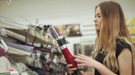selecionando : Female customer wants to buy new curling iron for her hairstyle. Woman checks the quality of a new iron. Shopping for a beauty tools.