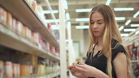 conventional : Alone young woman is holding incandescent lamp in hands in a hall of supermarket. She is getting it from paper box and checking a spiral Stock Footage