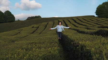 the azores : Slow motion shot of stylish brunette woman running on the tea plantation in summer. Happy girl enjoying spending time outside in nature.