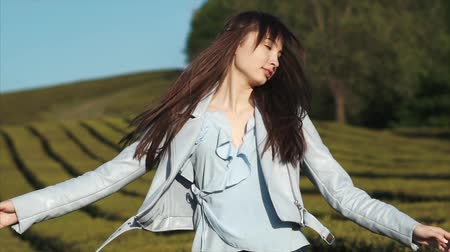 hair growth : Beautiful brunette woman in stylish outfit walking on tea plantation in summer. Taking pleasure and positive lifestyle.