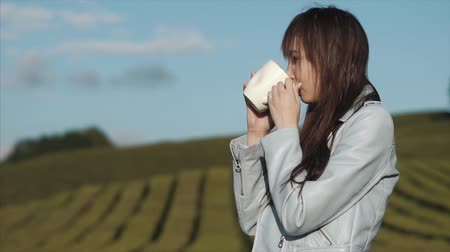 soluma : Young brunette woman is drinking hot tea from a mug standing outdoors in nature. She is breathing fresh air of mountain on a tea plantation