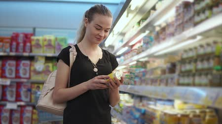 pot stickers : Blonde woman is taking glass pot with puree for children in a supermarket. She is looking on sticker, examining composition