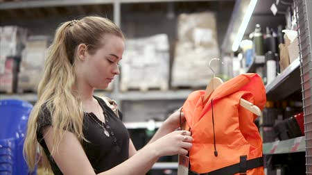 shelf life : Young woman is holding orange life vest on a hanger and touching it. She is standing in a department of hypermarket near shelves