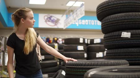 yedek : Woman is choosing new tires for her car in autoshop. Female car driver looking for new tires in the store. Shopping for the car.