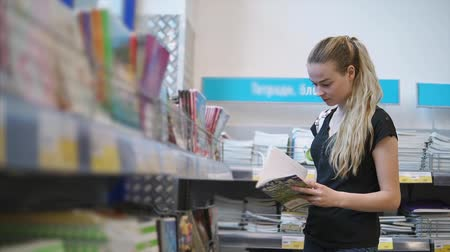schooler : Pretty young woman is regarding sheets of album in a office supplies department. Preparing and shopping for educational year Stock Footage