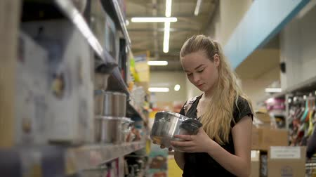 coisa : Young housewife is choosing metal saucepans in supermarket. She is smiling, taking two items on hands and watching on them