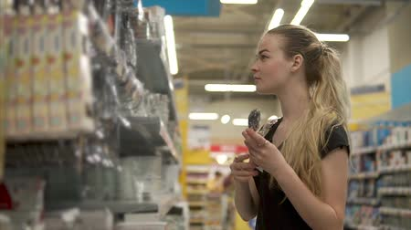 cserépedény : Lovely girl shopping for tableware in the supermarket. Female customer buying new stuff for the kitchen. Spoons, forks and knives.