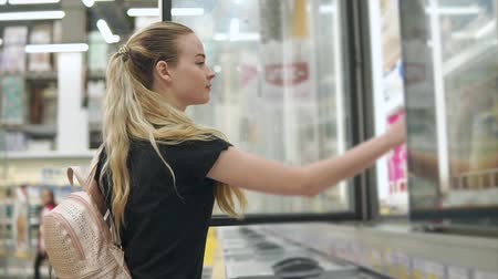 supermarket food : Beautiful young woman buying frozen yogurt in a supermarket. Customer takes yogurt from a fridge in store. Sweet snack. Consumer goods. Stock Footage