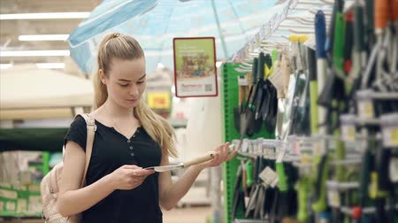 secateur : Lovely young girl choosing new gardening tools in a store. Variety of shovels and racks. Shopping for tools for gardening. Stock Footage