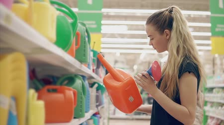 bailer : Blonde girl is examing a plastic watering can for pouring plants on a villa. She is standing in a hall of big store, preparing for summer season