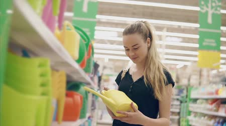 secateur : Young blonde girls spending time in the store looking for new water sprinkler can for the garden. Woman chooses new water sprinkler can for watering flowers.