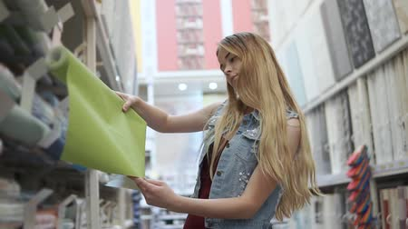 levou : Alone blonde girl is rotating a coil of wallpaper in a building materials store. She is choosing color for design in her apartment
