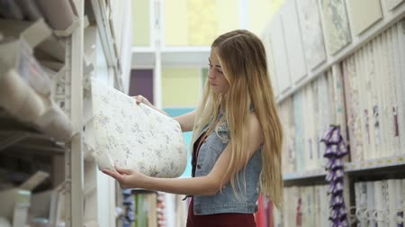 dolgok : Young woman is unwrapping roll with wallcovering in a building store. She is thinking about repair in her room and smiling