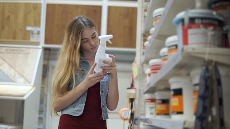 dyes : Young woman is getting a vial with chemical from shelf in a shop. She is reading inscription on a label, standing in a department with paints for repair Stock Footage