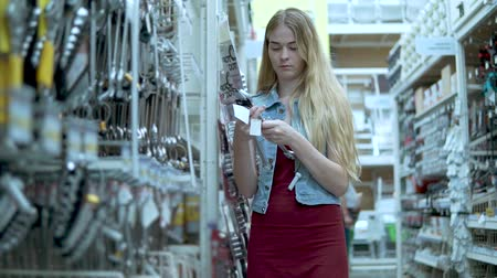 スパナ : Slim blonde girl is choosing a size of wrench in a supermarket. She is holding one in hands, spinning, then taking bigger