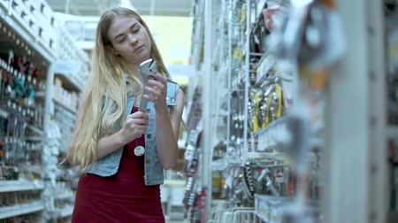 İngiliz anahtarı : Portrait of a blonde woman choosing a building tools in a hardware store. Woman holding a big metal wrench. Purchase in building store. Building tools.