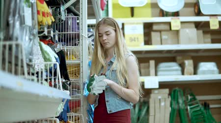 see off : Blonde girl is looking for a gloves with rubber cover in a shop. She is taking model from hanger on shelf and feeling it